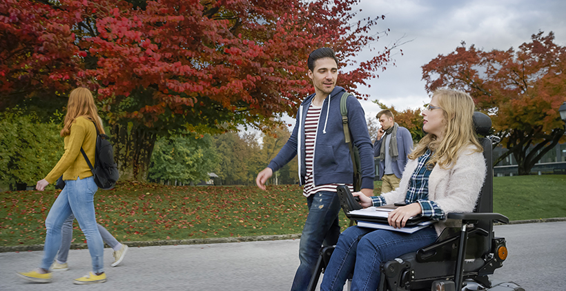 Male student talking with female student sitting on powered wheelchair at university campus.