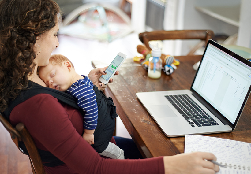 Photo of a woman holding a sleeping infant while checking her cellphone and sitting in front of her laptop