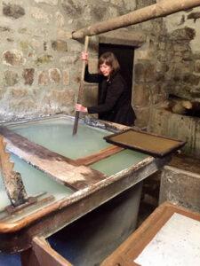 Joyce Kinkead making paper in a 14th century paper mill near Ambert, France (2018).