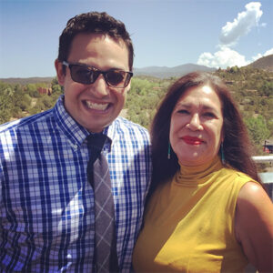 A photo of Cruz Medina with Ana Castillo in Santa Fe in 2016, taken outside with clouds in the background.